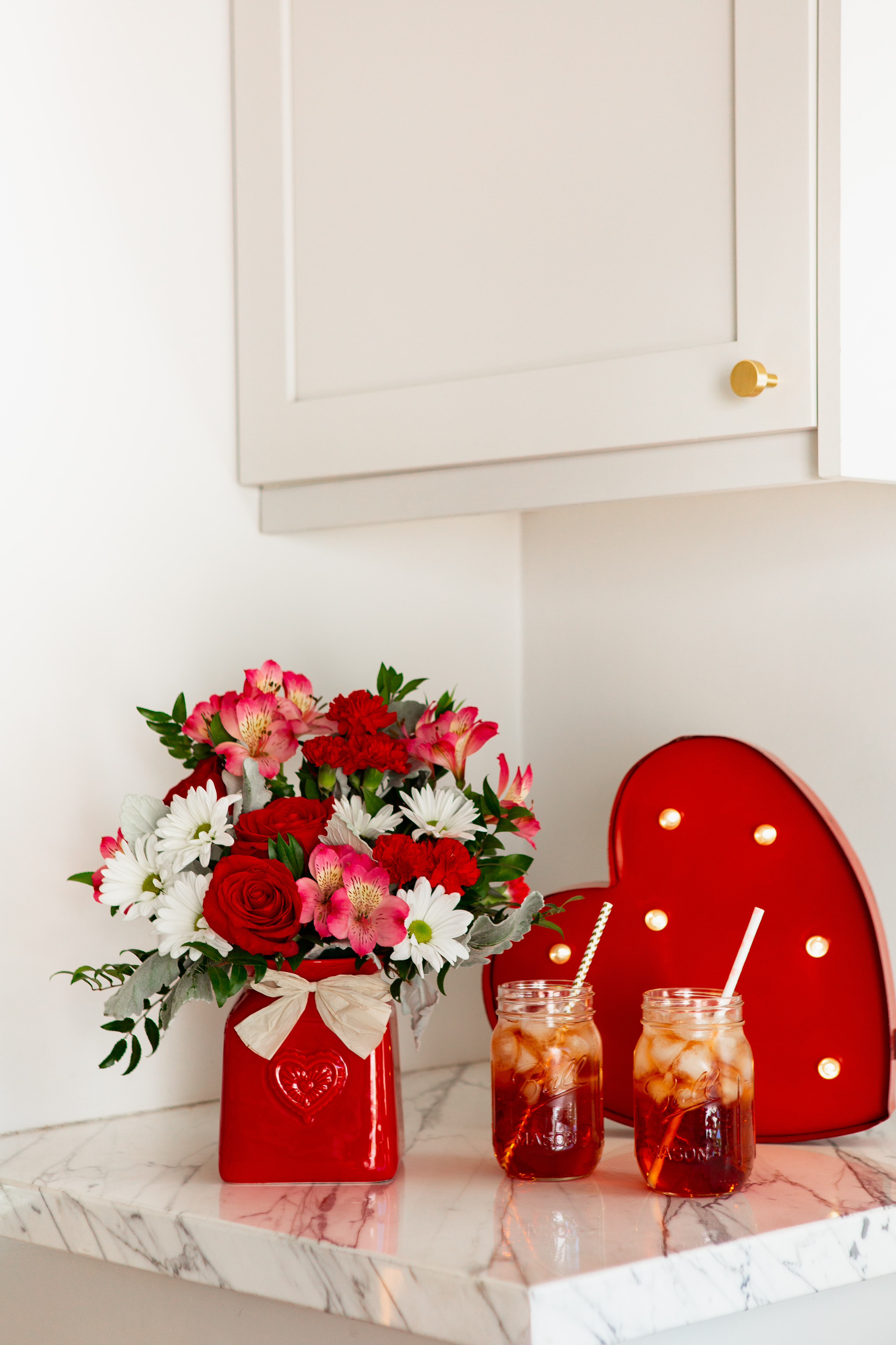 Red and pink flowers in pink crock vase next to ice tea glasses and a red heart