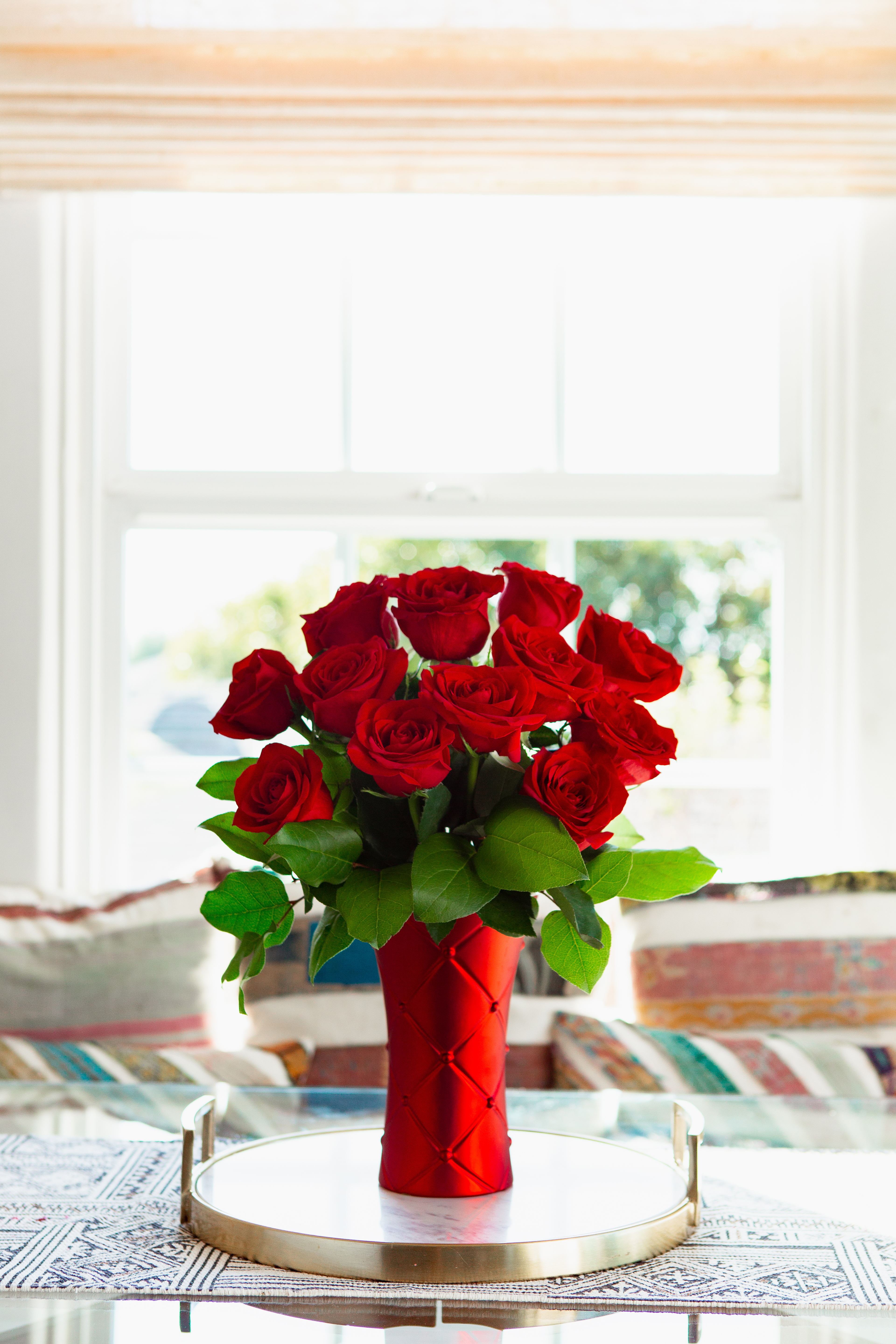 red roses in red vase on table