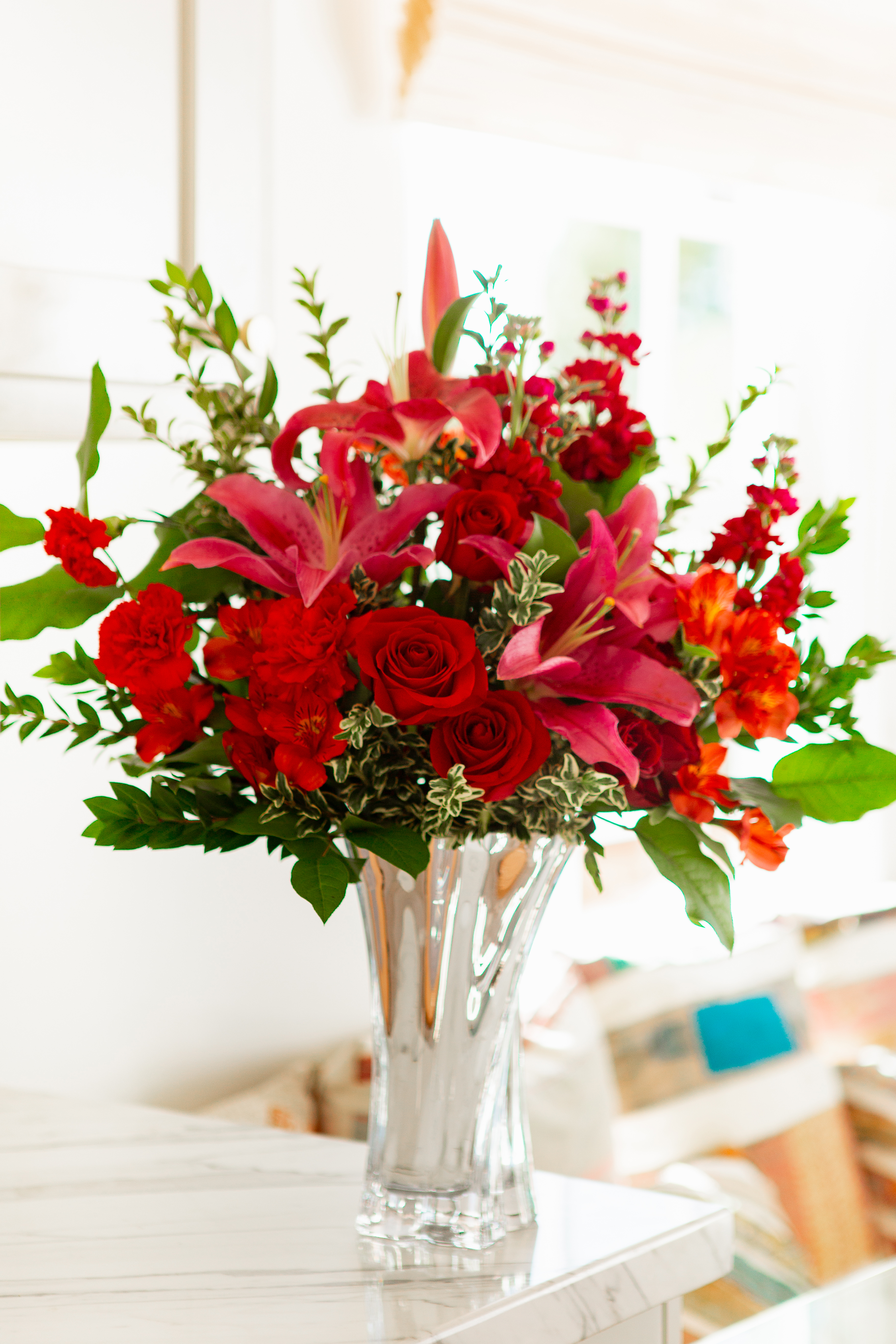 Pink lilies and red roses with greenery in silver vase on table