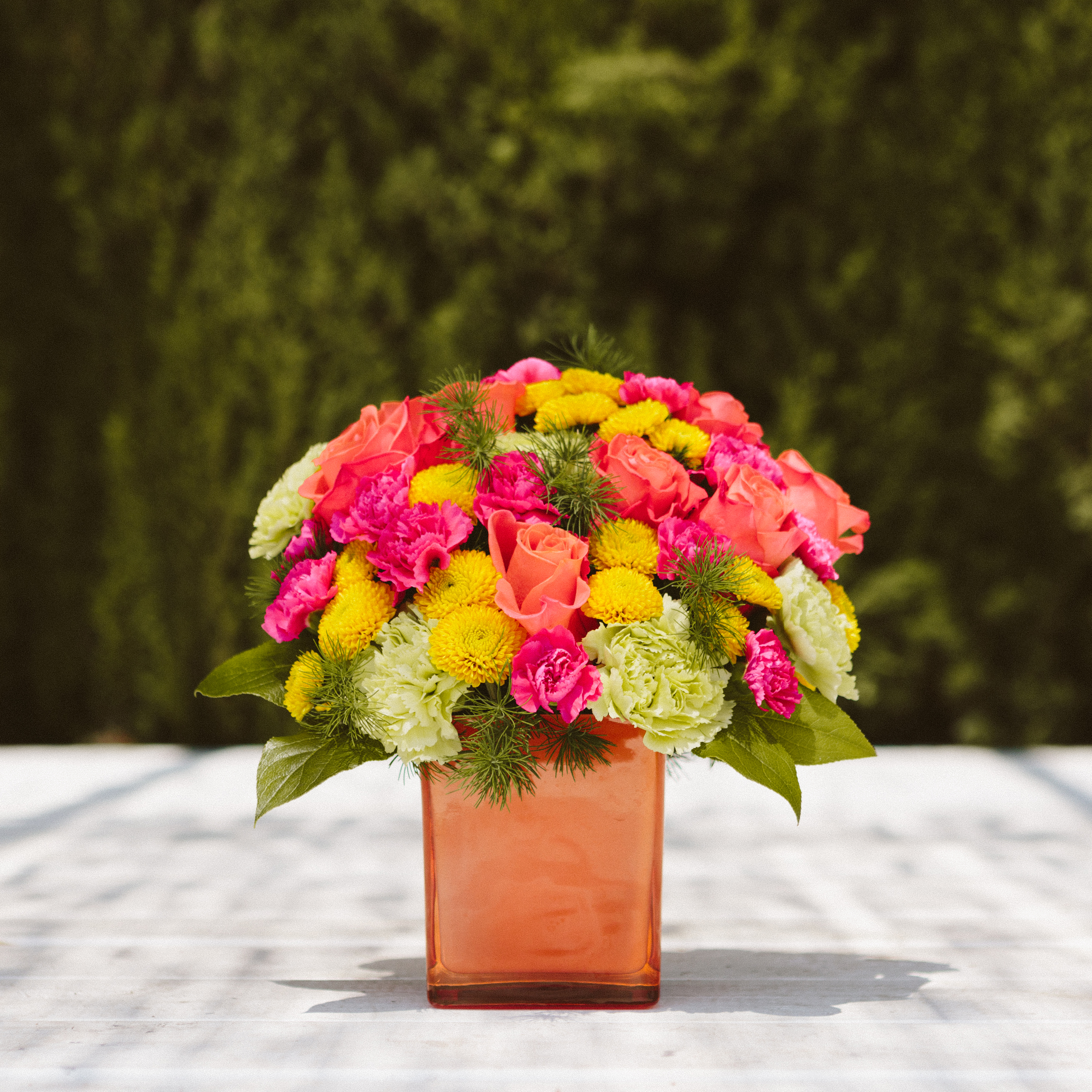 Orange cube vase filled with orange roses, yellow mums, green carnations and more on outdoor table