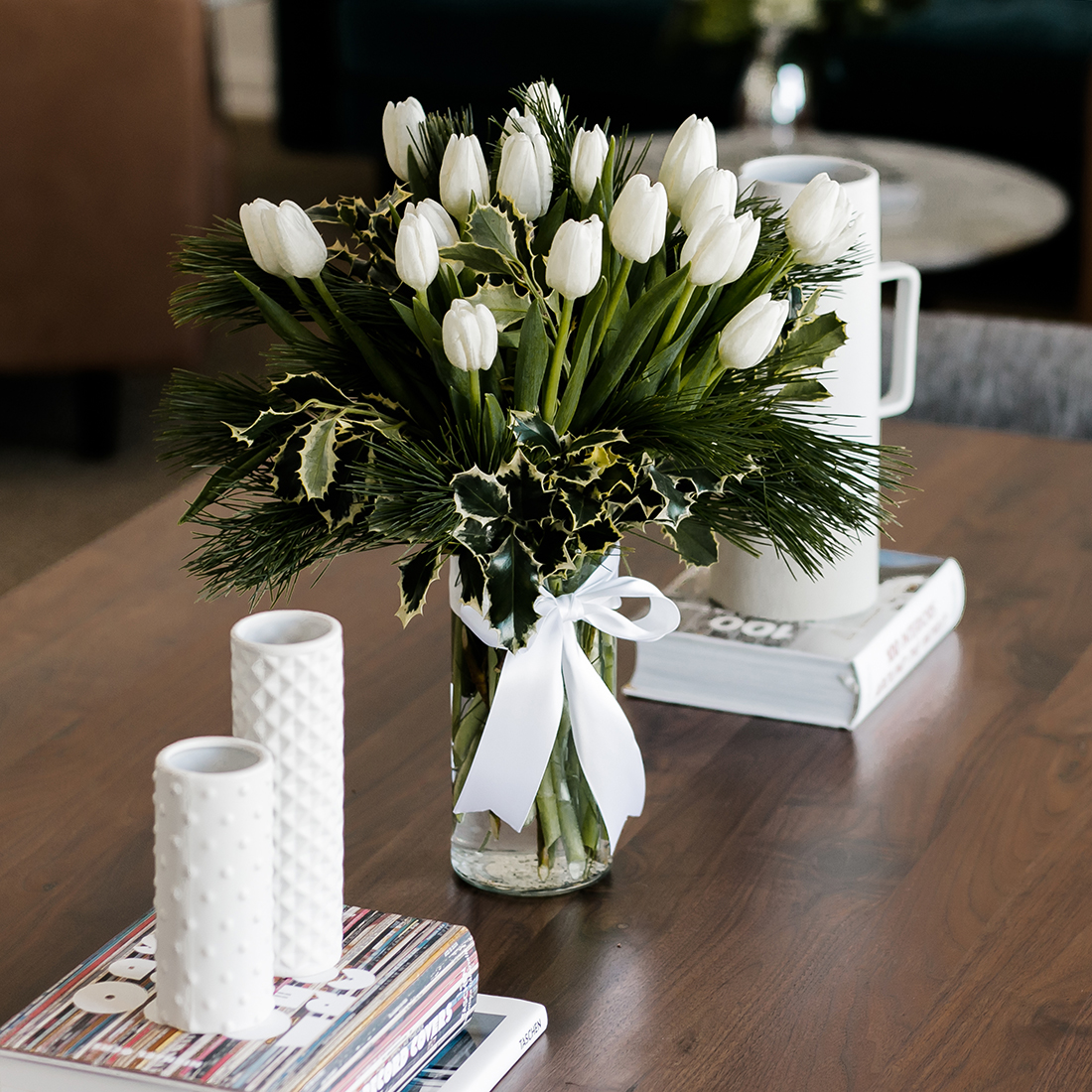 White tulips and greenery in a clear vase with white ribbon on wood table with books and candles