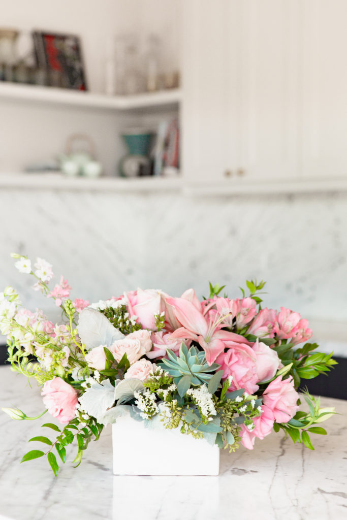 Succulents, pink roses, pink lilies, and more fill a bamboo container