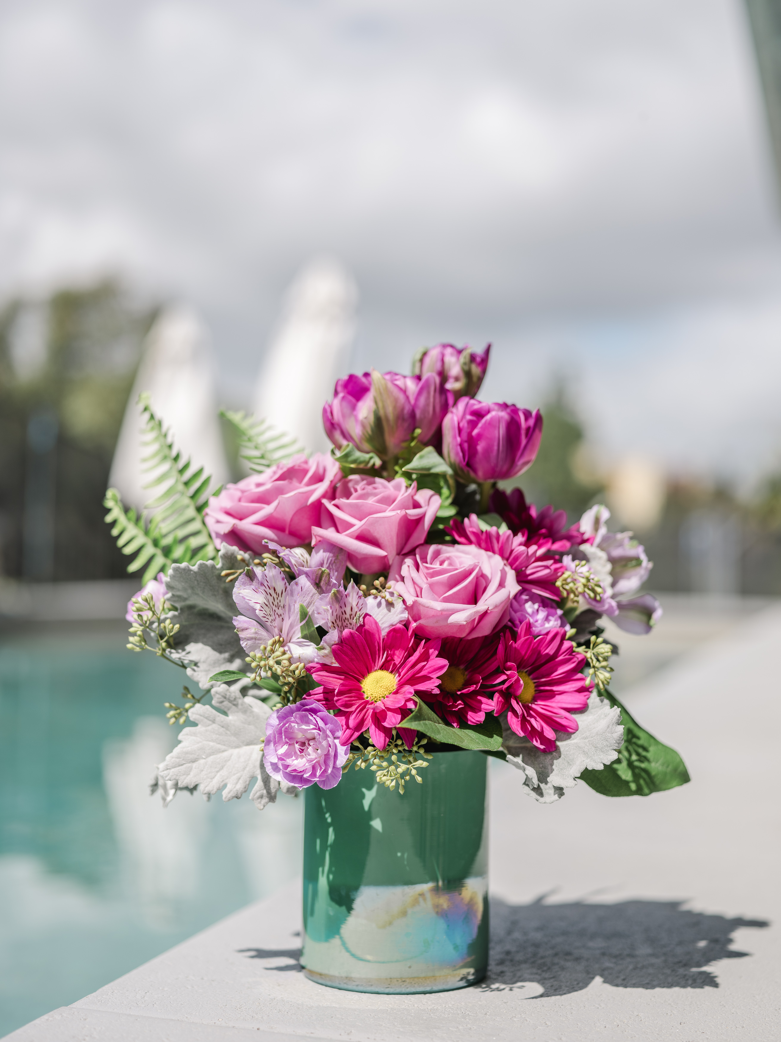 pink roses, pink carnations, purple flowers, and more in a blue glass vase sitting by a pool