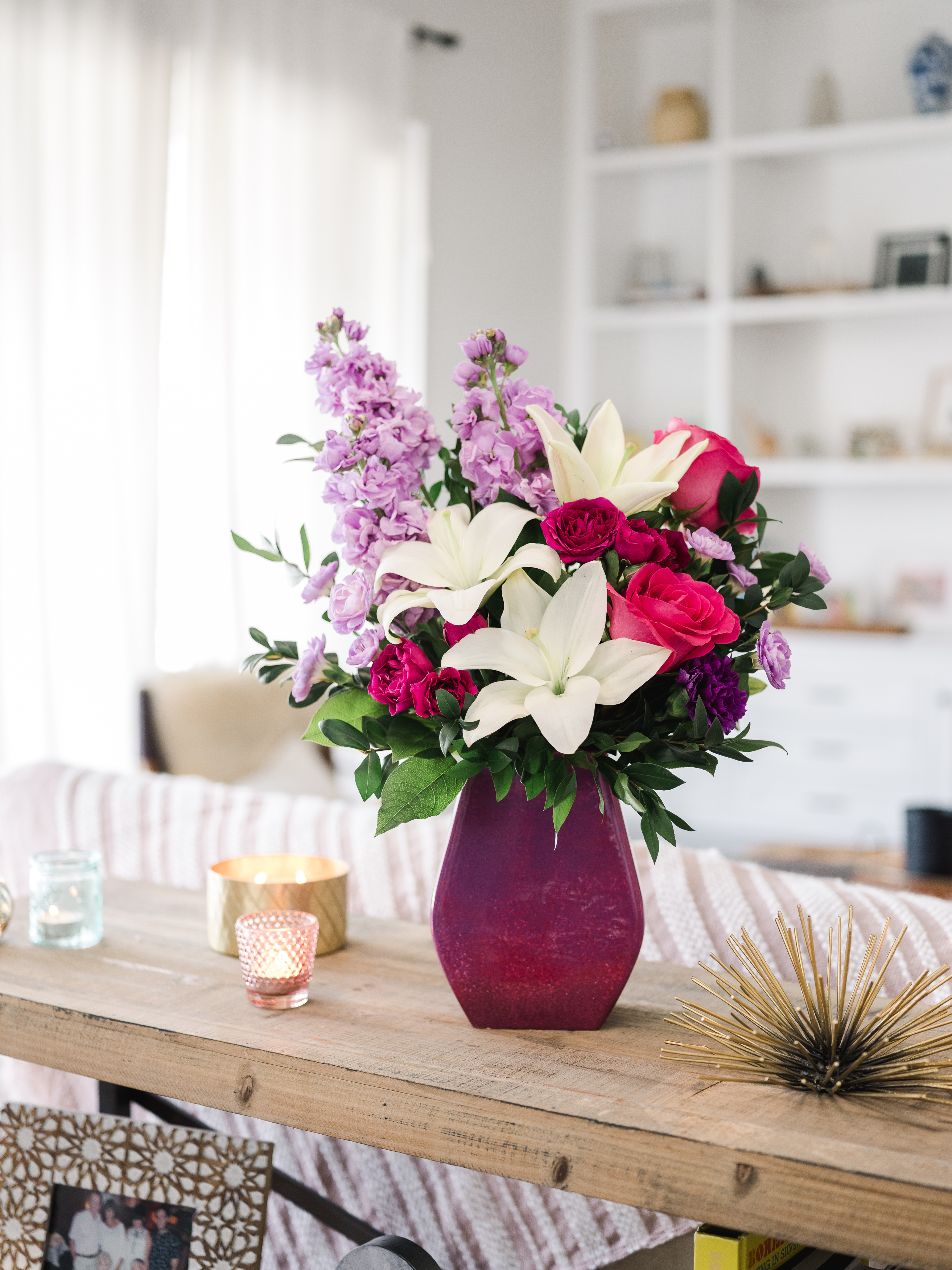 White lilies, pink roses, purple statice, and more fill a vibrant purple vase on a coffee table with trinkets