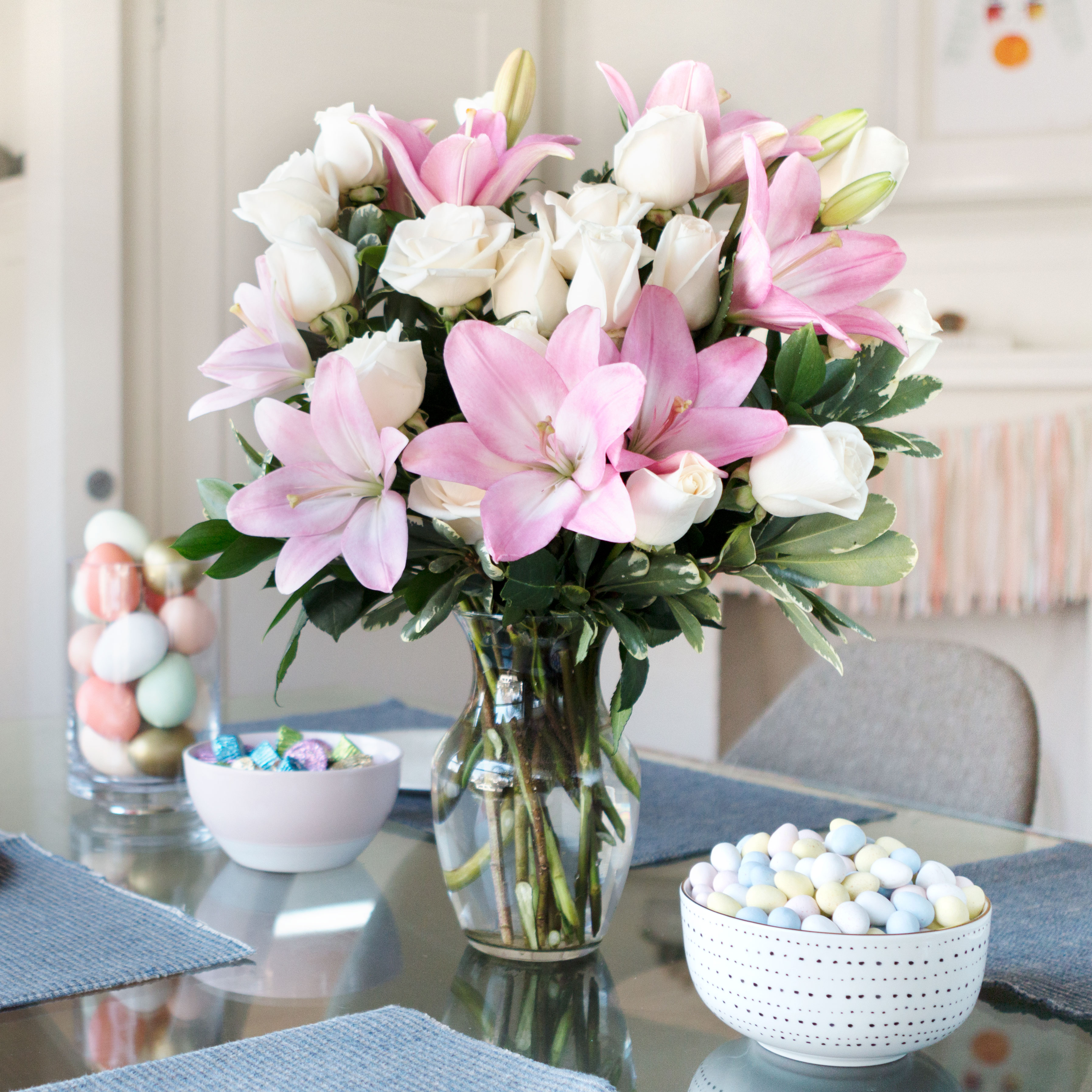 Pink lilies, white roses, and more in clear vase on Easter table with chocolate