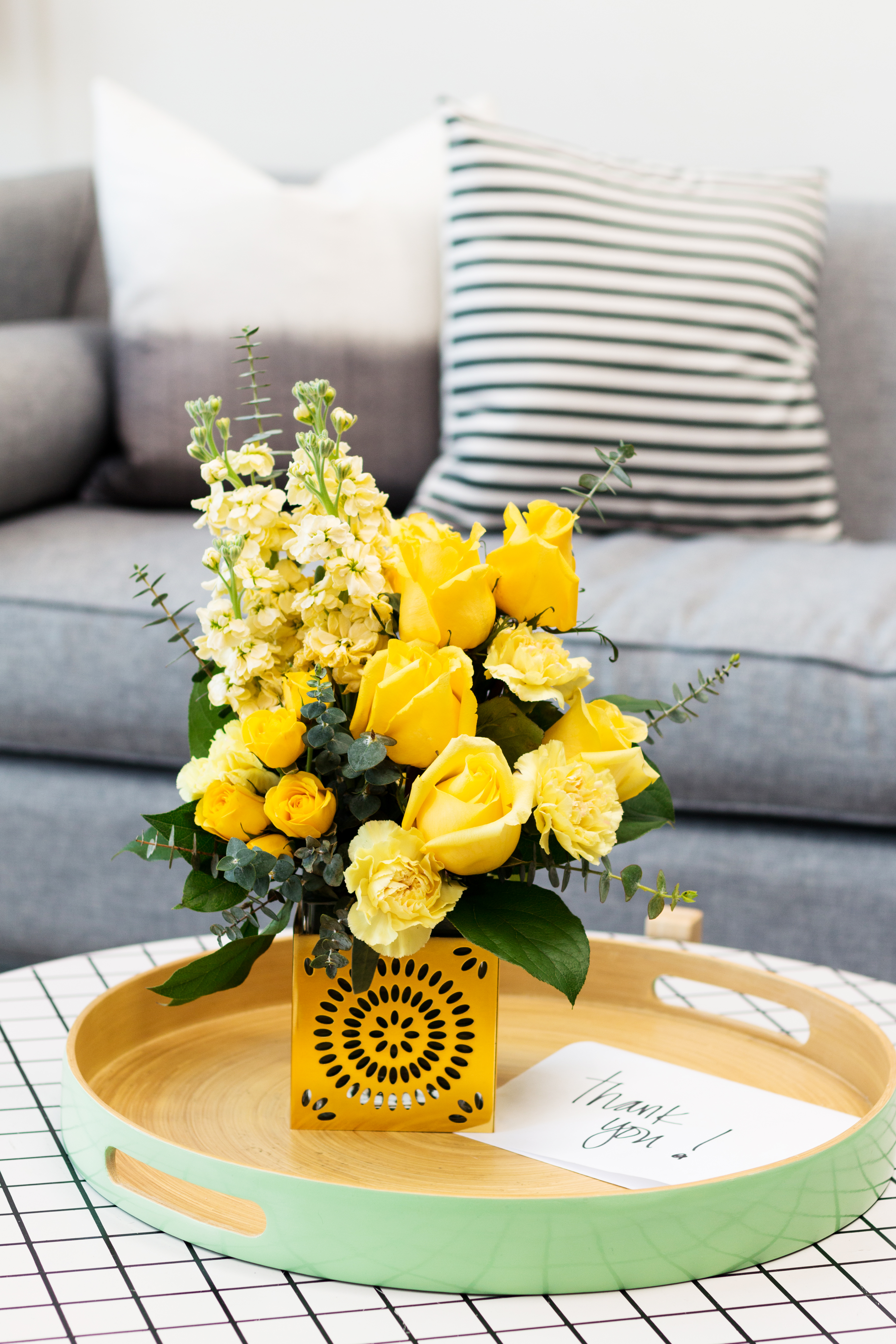 yellow roses and carnations fill a gold cube vase on a table with thank you card