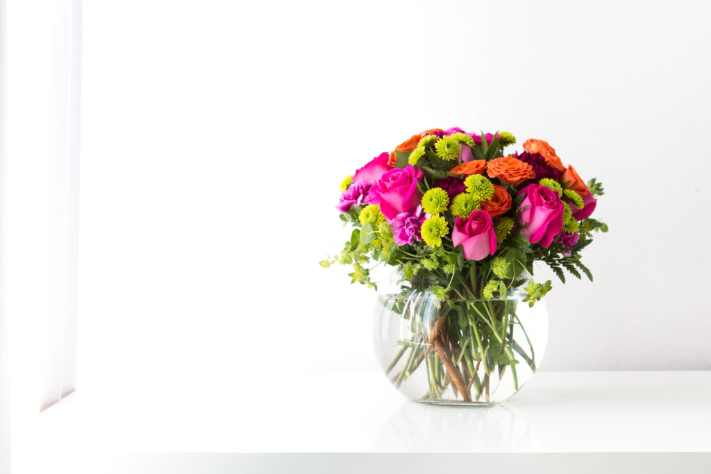 pink roses, green mums, orange roses, and more fill a clear vase