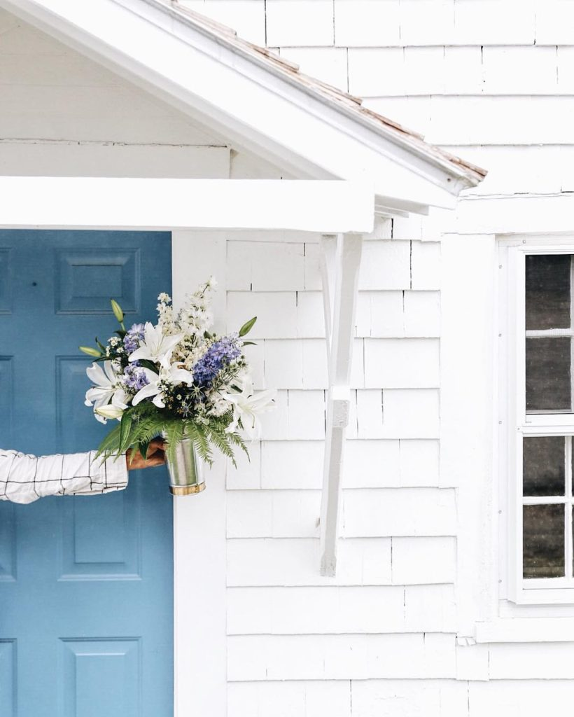 White and blue flowers fill a metal can sitting outside a blue door