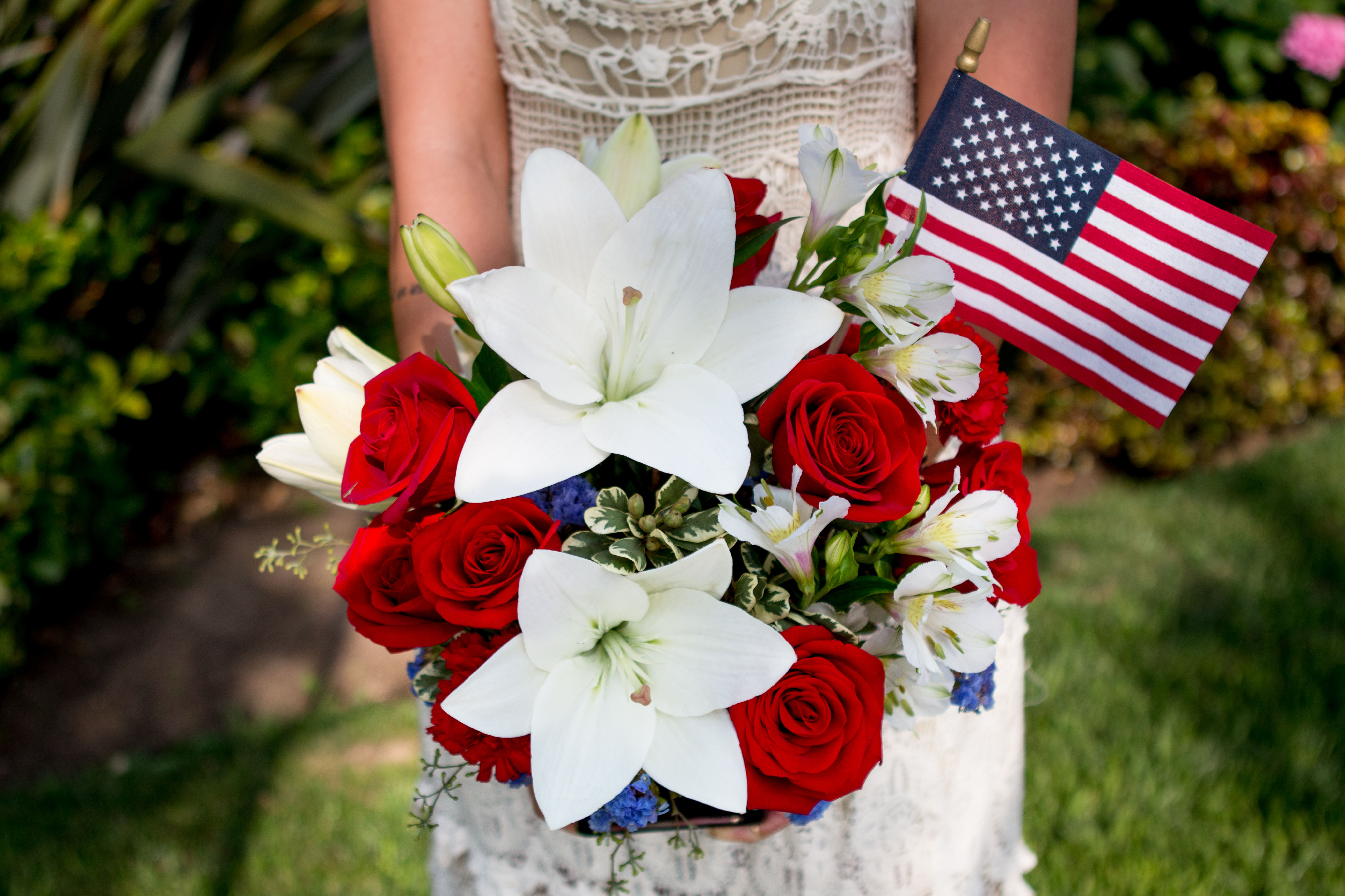 white lilies, red roses, and more in a lady's hands with an American flag