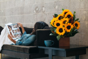 sunflowers in a bamboo container next to a girl laying on the couch