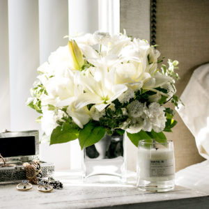 white lilies and white roses in a cube vase on a nightstand with candles and jewelry in a