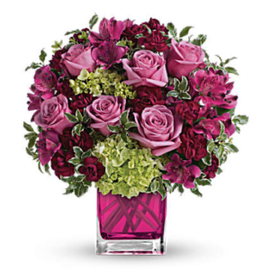 lavender roses, hydrangea, maroon carnations, and more fill a magenta cube vase