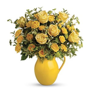 yellow roses, white carnations, yellow daisies, and more fill a yellow pitcher