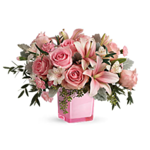 pink lilies, pink roses, greenery, and more fill a pink cube vase
