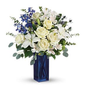 White lilies, white roses, greenery, and eucalyptus fill a cobalt blue vase