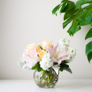 pink lilies, creme roses, white stock and more in a clear bubble vase