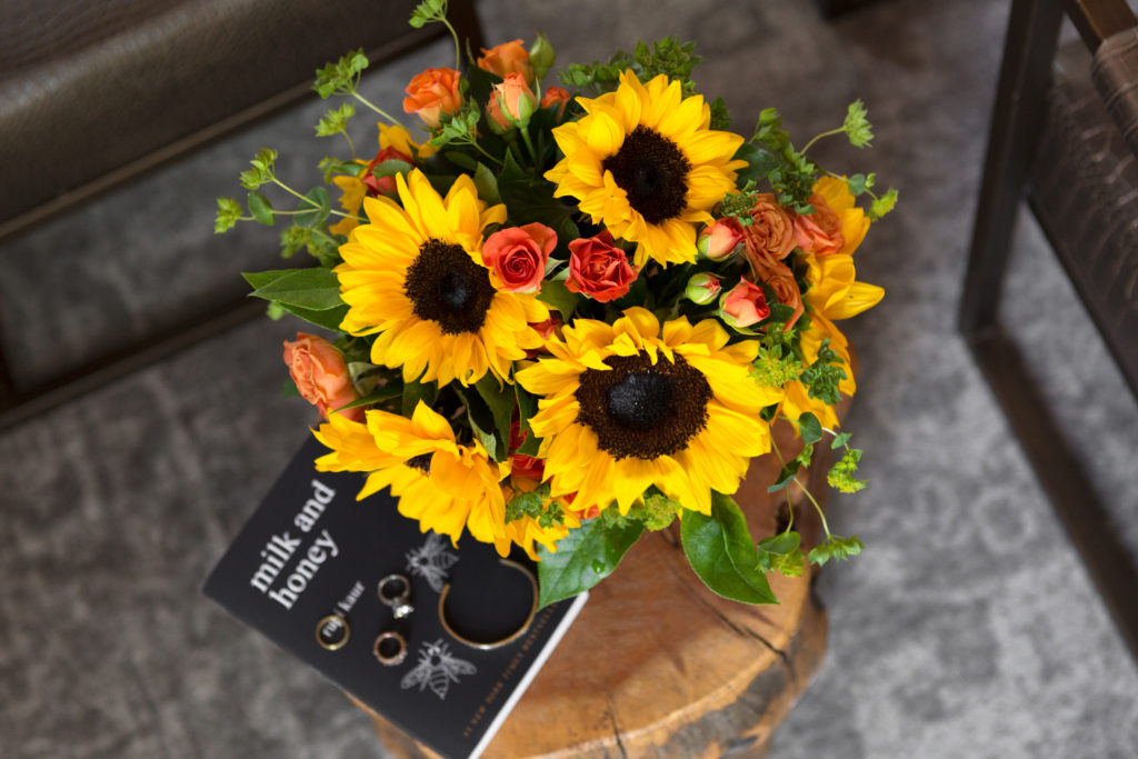 closeup of sunflowers, orange roses, and greenery on a tree stump