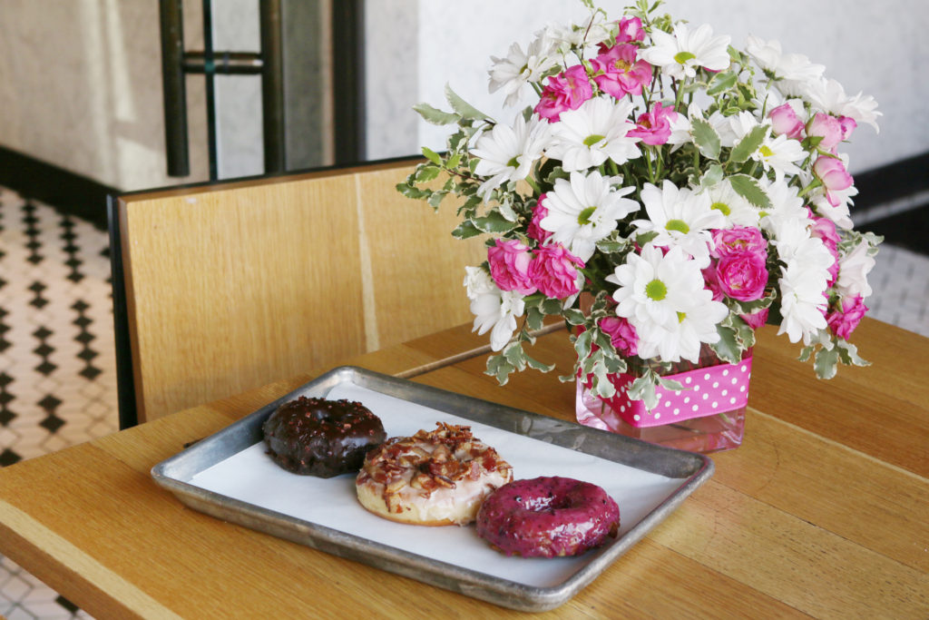 3 donuts on a tray next to white daises and pink carnations in a cube vase with pink ribbon