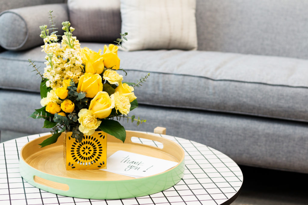 yellow roses, yellow carnations, and yellow stock fill a gold cub vase on a coffee table