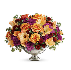 Orange roses, purple mums, orchids, and more mercury centerpiece.