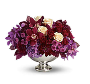 Purple dahlias, creme roses, purple mums and more fill a silver centerpiece