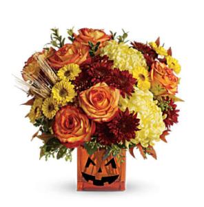 Orange roses, yellow spray mums, rust cushion spray mums, and more fill a jack-o-lantern cube vase