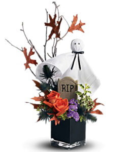 Orange, blue erynginum, purple statice, and more fill a black cube vase accented with a ghost