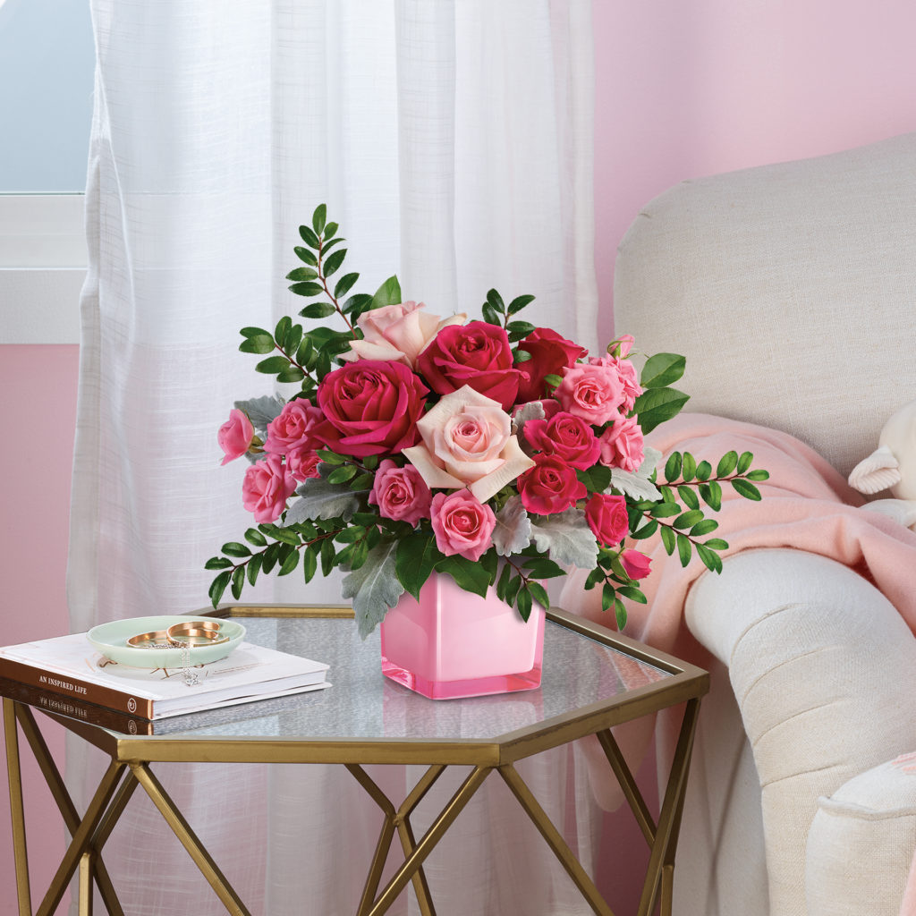 pink power bouquet on a side table filled with pink roses of all shades in a pink cube vase