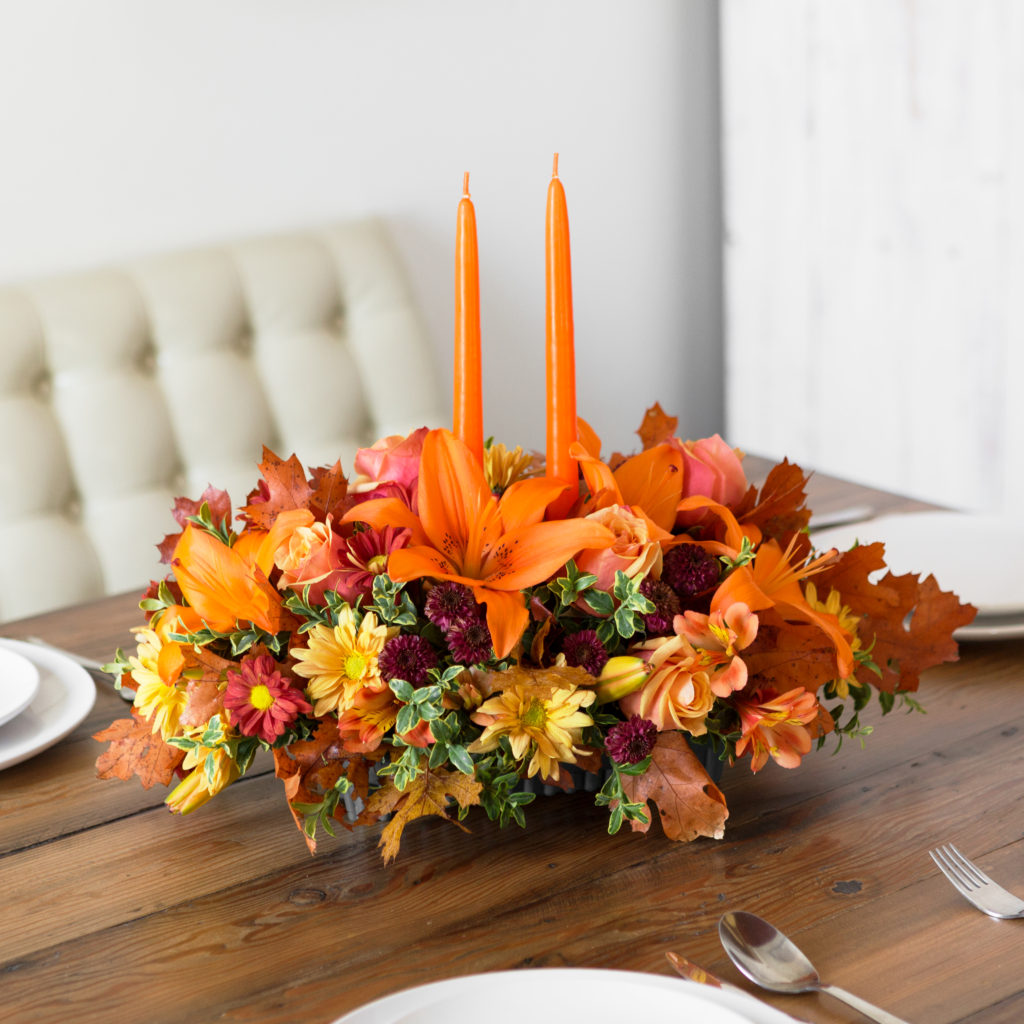 Orange lilies, yellow carnations, purple mums and more fill a thanksgiving centerpiece