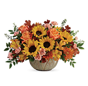 Yellow sunflowers, orange roses, peach carnations, and more fill a stoneware bowl centerpiece