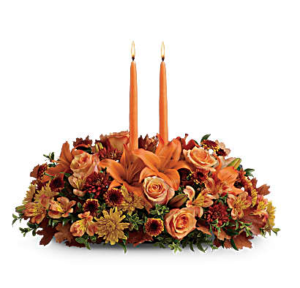 Orange rose, mums, lilies, and burgundy carnations fill a centerpiece with two candles