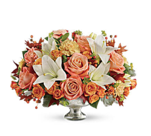 White lilies, orange roses, peach carnations and more fill a silver centerpiece