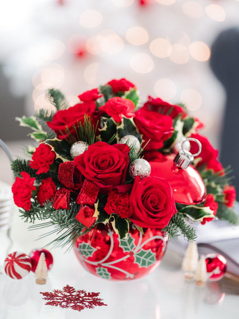 Red roses and carnations fill a red glass ornament vase