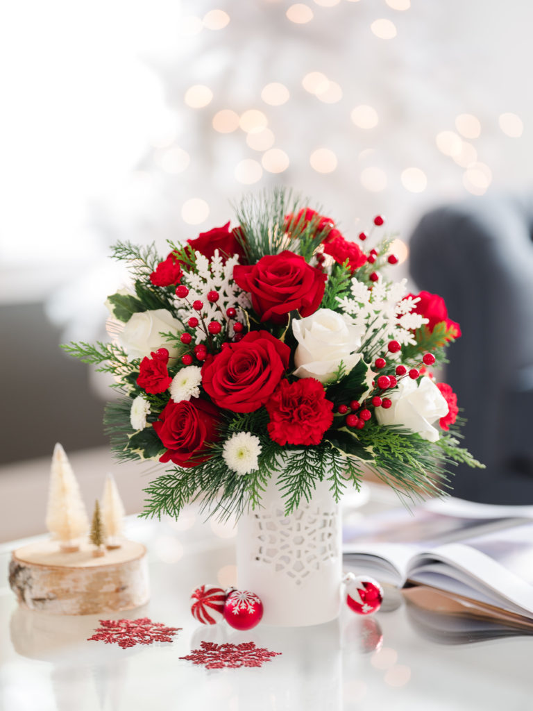 Red and white roses, red carnations, and white mums accented with fir fill a white snowflake vase