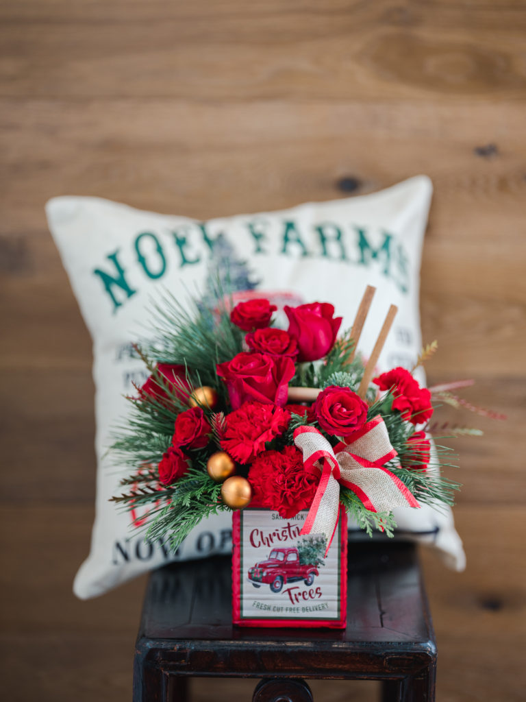 Red roses and carnations fill a vintage cube vase and accented with a burlap ribbon