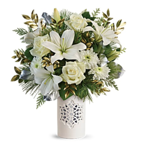 White roses, lilies, carnations, and more are accented with gold leaves and fill a white snowflake vase