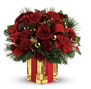 Red roses, red carnations, and pines fill a festive gold cube vase wrapped with ribbon