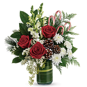 Red roses, white stock, white carnations, and more fill a clear vase accented with candy canes and pines