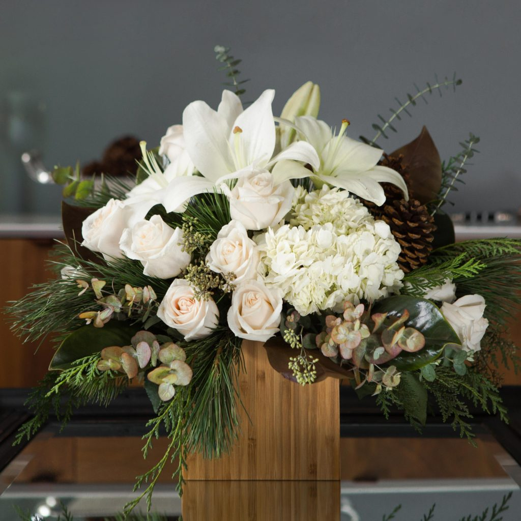 White lilies, hydrangea, roses, and more fill a bamboo container on a table