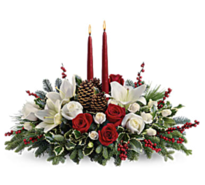 White liles, red roses, greenery, and more make up a Christmas centerpiece with red candles