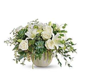 White roses, succulents, greenery, and more fill a ceramic bowl
