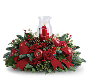 Red roses, apples, pinecones, greenery, and more surround a candle in a beautiful centerpiece