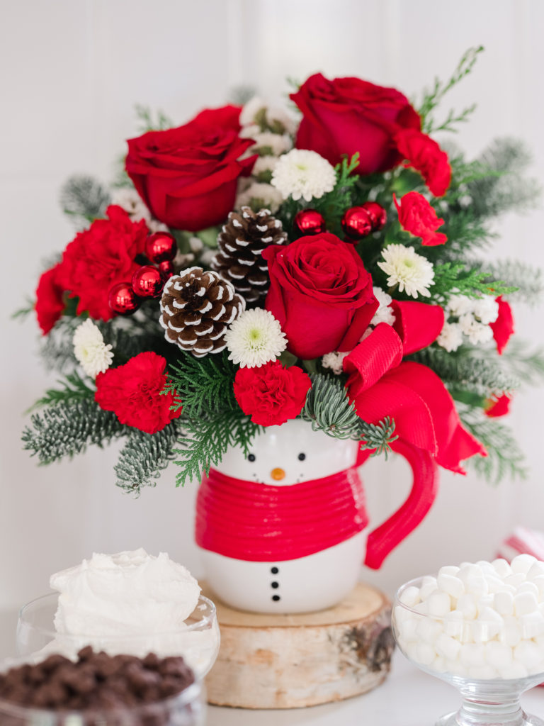 Red roses, white mums, and red carnations fill a snowman mug accented with fir and pines