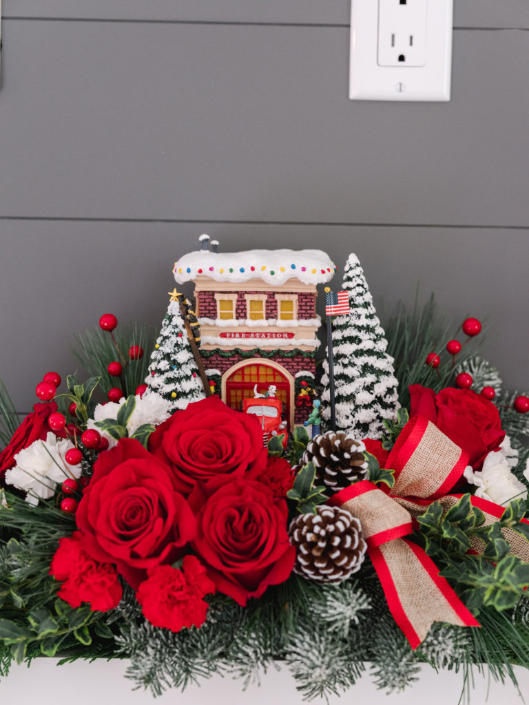 Red roses, fir, pinecones, and more surround a hand-painted resin of a firehouse