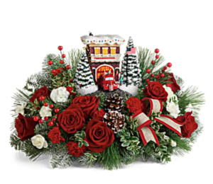 Red roses, white carnations, greenery, and more surround a hand-painted firehouse sculpture