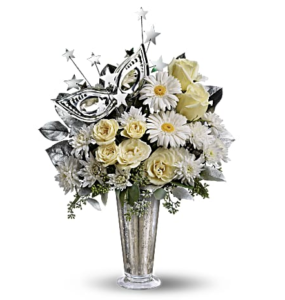 Creme roses, daisies, mums, and more fill a silver mercury glass vase accented with a masquerade mask