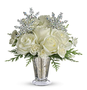 White roses and carnations fill a silver mercury glass vase and accented with silver snowflakes