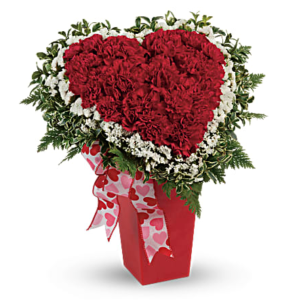 Red spray roses and white carnations make a heart shape in a red vase