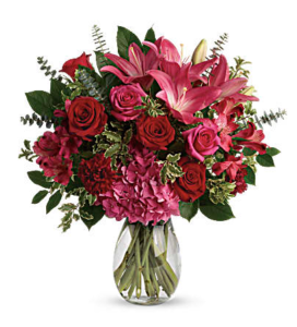 Hot pink lilies, pink and red roses, and red carnation fill a clear vase with greenery