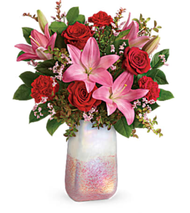 Pink lilies and red roses fill a rose quartz vase